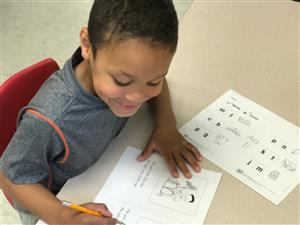 Kindergarten student reading and writing