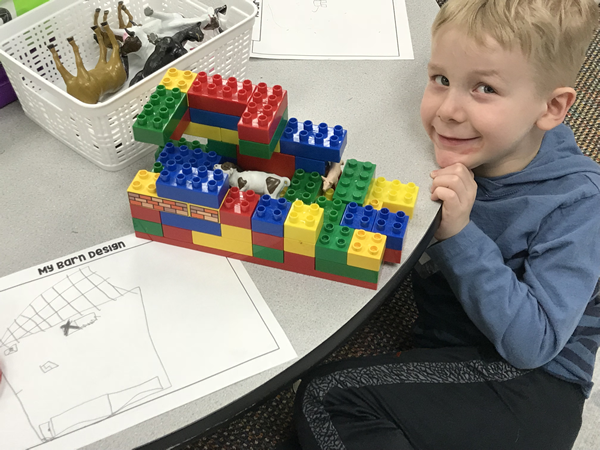 A Wilkshire student shows off the barn he built out of Legos.