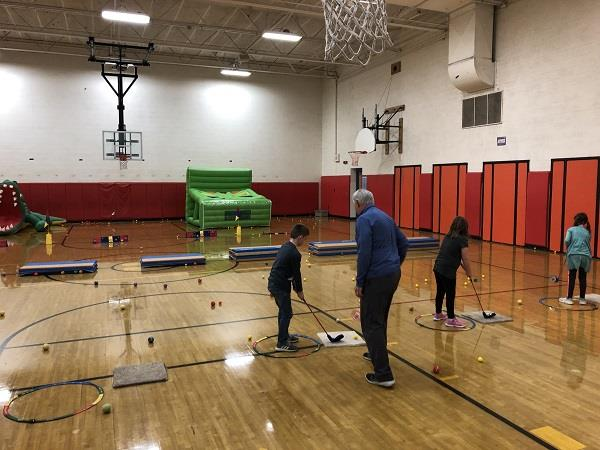 Golf Pro Gives Lessons to Students