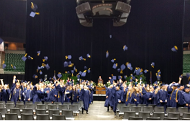 Students toss caps into air following graduation ceremony