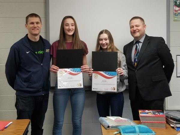 Middle School students Emily and Ella receive their essay contest awards.