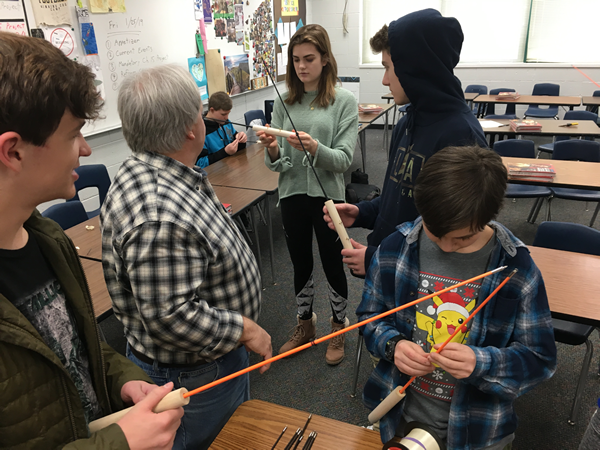Students learn how to make ice fishing poles.